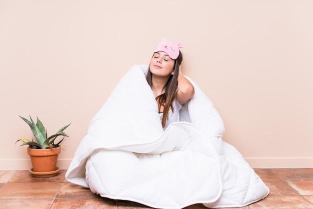 Jonge blanke vrouw rusten met een dekbed aan te raken achterkant van het hoofd, denken en het maken van een keuze.
