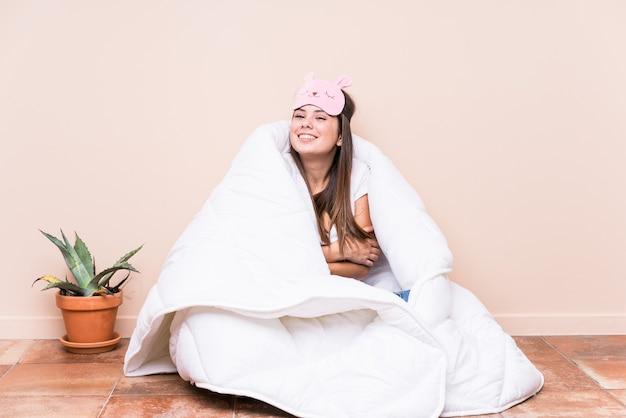 Jonge blanke vrouw rusten met een quilt lachen en plezier maken.