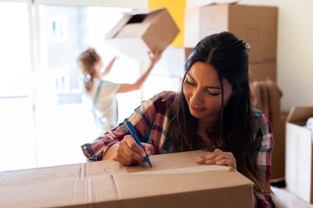 Jonge blanke vrouw schrijft label op kartonnen doos voor verhuizing kopieer ruimte verhuisconcept