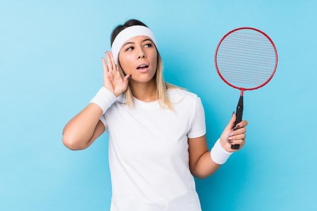 Jonge blanke vrouw spelen badminton geïsoleerd proberen te luisteren een roddels.