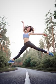 Jonge blanke vrouw springen asfaltweg zonnige zomerochtend