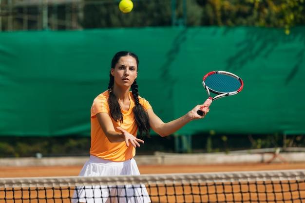 Jonge blanke vrouw tennissen op tennisbaan buitenshuis.