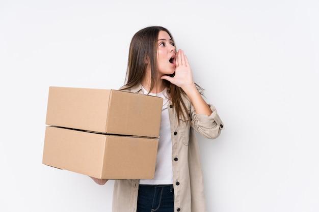 Jonge blanke vrouw verhuizen naar een nieuw huis schreeuwen en houden palm in de buurt van geopende mond.