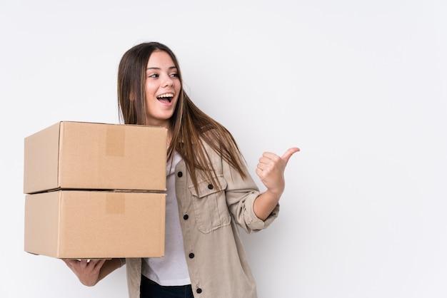 Jonge blanke vrouw verhuizen naar een nieuw huis wijst met duim vinger weg, lachen en zorgeloos