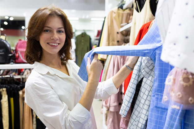 Jonge blanke vrouw verkoop assistent helpt om shirt te kiezen