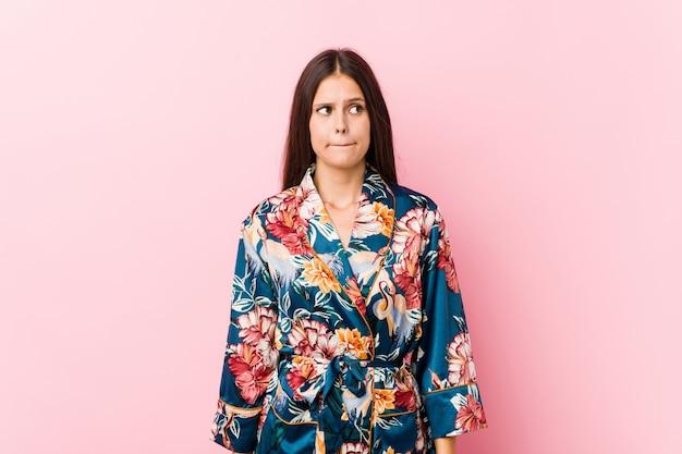 Jonge blanke vrouw, verward met een kimono pyjama, voelt zich twijfelachtig en onzeker.
