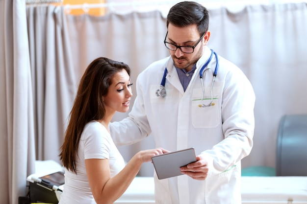 Jonge blanke vrouw wijzend op tablet en vragen haar arts.
