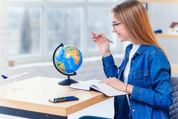 Jonge blanke vrouw zit aan de tafel en draait de hele wereld om het land voor vakantie te kiezen en notities te maken in het notitieboek.