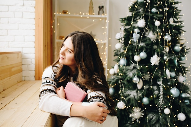Jonge blanke vrouw zit naast mooie versierde kerstboom met een boek en dromen