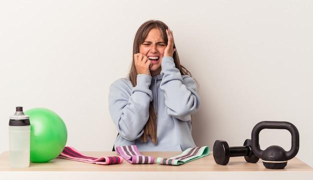 Jonge blanke vrouw zitten aan een tafel met sportuitrusting geïsoleerd op een witte achtergrond jammerend en huilend troosteloos.