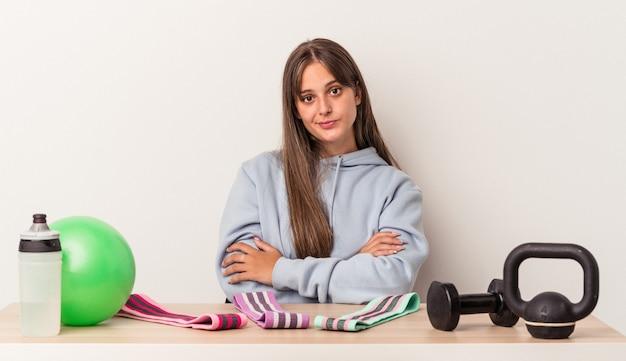 Jonge blanke vrouw zitten aan een tafel met sportuitrusting geïsoleerd op een witte achtergrond ongelukkig in de camera kijken met sarcastische uitdrukking.