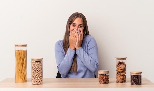 Jonge blanke vrouw zitten aan een tafel met voedsel pot geïsoleerd op een witte achtergrond lachen om iets, mond bedekken met handen.