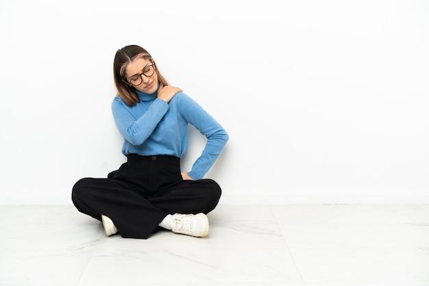 Jonge blanke vrouw zittend op de vloer die lijdt aan pijn in de schouder omdat ze zich heeft ingespannen