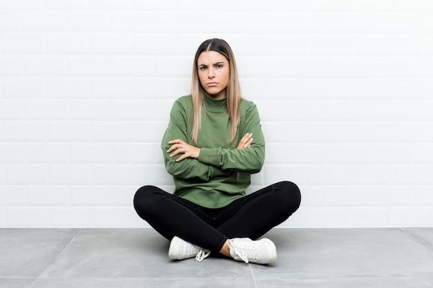 Jonge blanke vrouw zittend op de vloer fronsen gezicht in ongenoegen, houdt armen gevouwen.