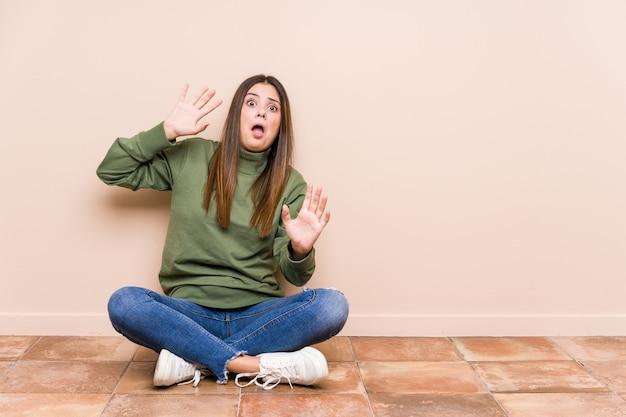 Jonge blanke vrouw zittend op de vloer geïsoleerd geschokt als gevolg van een dreigend gevaar