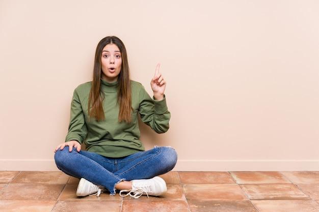 Jonge blanke vrouw zittend op de vloer geïsoleerd met een geweldig idee