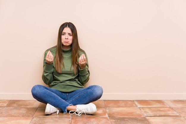 Jonge blanke vrouw zittend op de vloer geïsoleerd waaruit blijkt dat ze geen geld heeft.