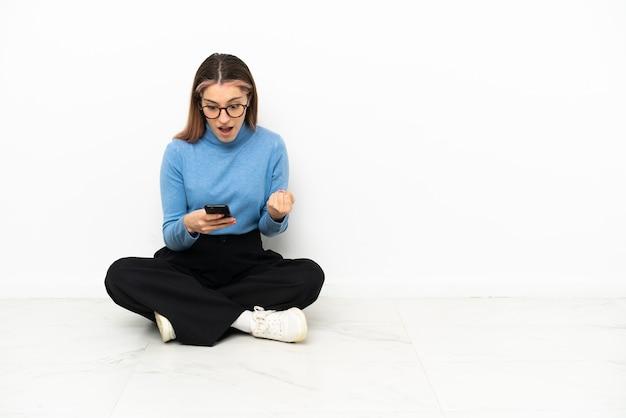 Jonge blanke vrouw zittend op de vloer verrast en een bericht verzenden