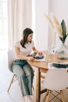 Jonge blanke vrouw zittend op een stoel aan de keukentafel thuis.