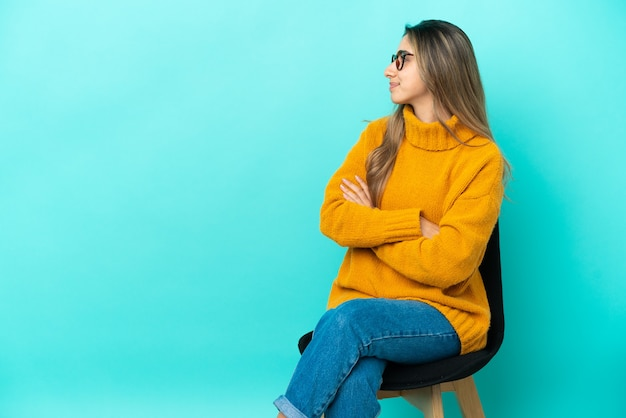 Jonge blanke vrouw zittend op een stoel geïsoleerd op een blauwe achtergrond in laterale positie