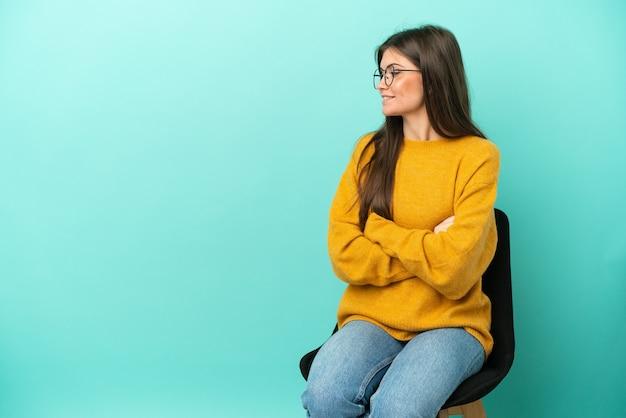Jonge blanke vrouw zittend op een stoel geïsoleerd op een blauwe achtergrond in zijpositie in
