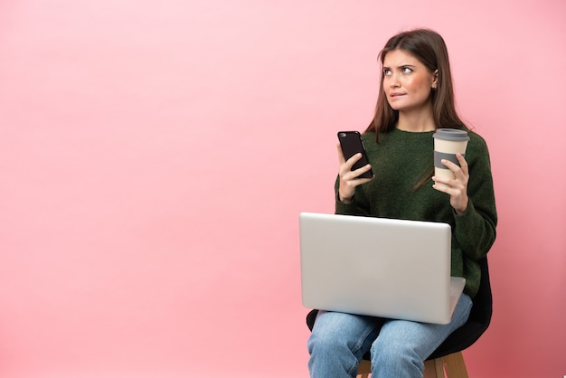 Jonge blanke vrouw zittend op een stoel met haar laptop geïsoleerd op roze achtergrond koffie te houden om mee te nemen en een mobiel terwijl ze iets denkt