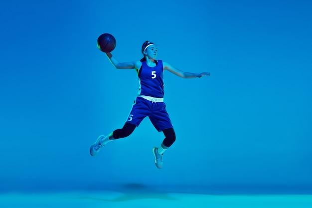 Jonge blanke vrouwelijke basketbalspeler geïsoleerd op blauw in neonlicht