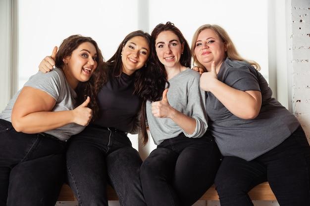 Jonge blanke vrouwen in vrijetijdskleding die samen plezier hebben. vrienden die bij het raam zitten en lachen, samen tijd doorbrengen. bodypositive, voeding, feminisme, van zichzelf houden, schoonheidsconcept.