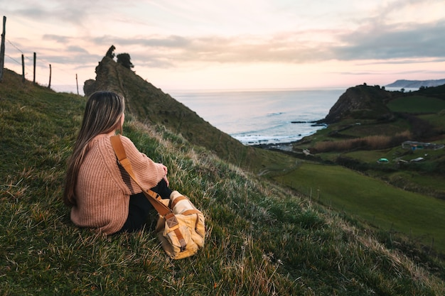 Jonge blanke vrouwenreiziger die een kustgebied in baskenland bezoekt.