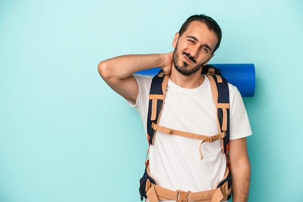 Jonge blanke wandelaar man geïsoleerd op blauwe achtergrond achterhoofd aanraken, denken en een keuze maken.