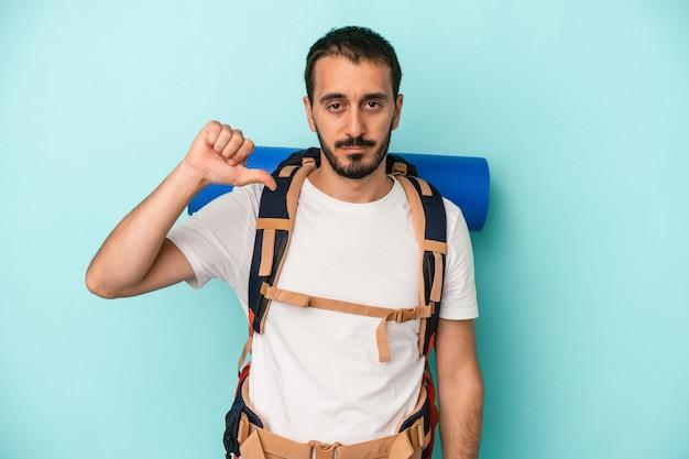 Jonge blanke wandelaar man geïsoleerd op blauwe achtergrond met een afkeer gebaar, duim omlaag. onenigheid begrip.