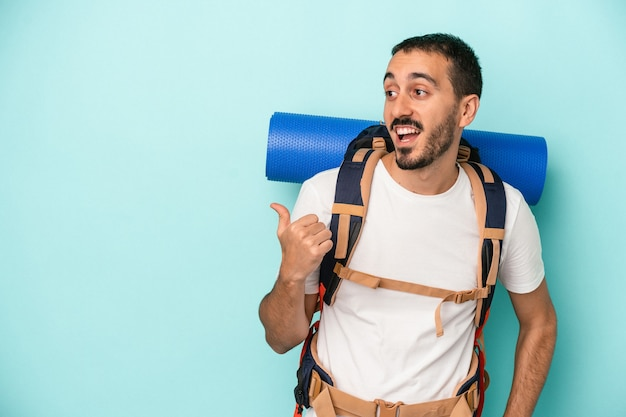 Jonge blanke wandelaar man geïsoleerd op blauwe achtergrond wijst met duimvinger weg, lachend en zorgeloos.