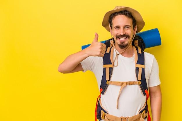 Jonge blanke wandelaar man geïsoleerd op gele achtergrond glimlachend en duim omhoog