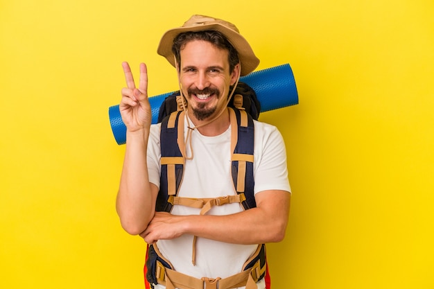 Jonge blanke wandelaar man geïsoleerd op gele achtergrond met nummer twee met vingers.