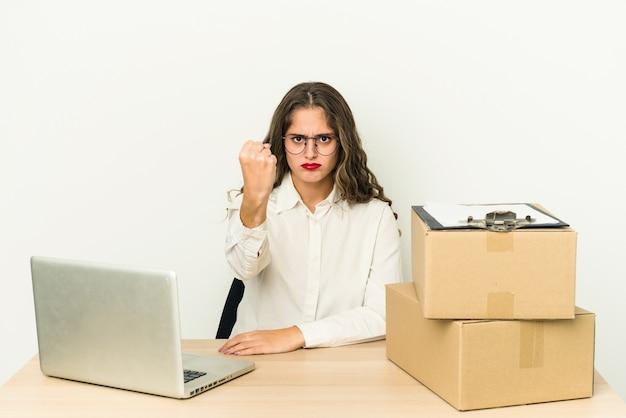 Jonge blanke werknemer van een pakketbedrijf geïsoleerd met vuist naar camera, agressieve gezichtsuitdrukking.