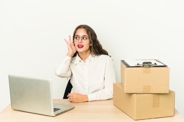 Jonge blanke werknemer van een pakketbedrijf geïsoleerd proberend een roddel te luisteren