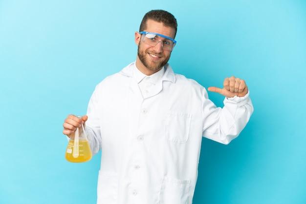 Jonge blanke wetenschappelijke man geïsoleerd op blauwe achtergrond trots en zelfvoldaan