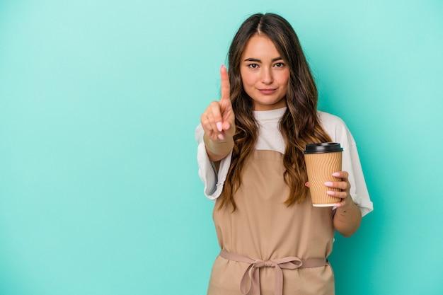 Jonge blanke winkelbediende vrouw met een afhaalmaaltijden koffie geïsoleerd op blauwe achtergrond met nummer één met vinger.