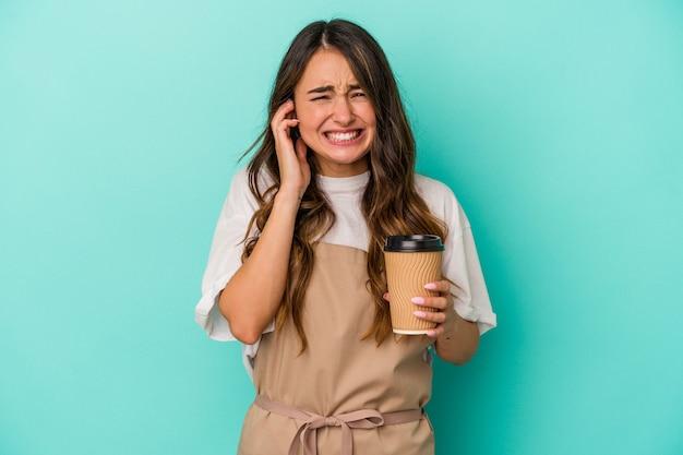 Jonge blanke winkelbediende vrouw met een afhaalmaaltijden koffie geïsoleerd op een blauwe achtergrond die oren bedekt met handen.