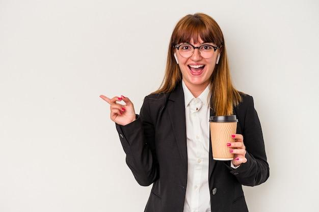 Jonge blanke zakelijke bochtige vrouw met een kopje koffie geïsoleerd op een witte achtergrond glimlachend en opzij wijzend, iets tonend op lege ruimte.