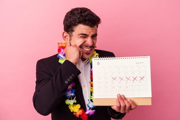 Jonge blanke zakenman die de dagen telt voor vakanties geïsoleerd op een roze achtergrond die oren bedekt met handen.