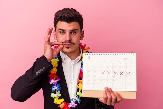 Jonge blanke zakenman die de dagen telt voor vakanties geïsoleerd op roze achtergrond met vingers op lippen die een geheim houden.