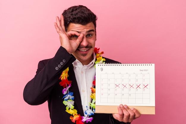 Jonge blanke zakenman die de dagen telt voor vakanties geïsoleerd op roze achtergrond opgewonden houden ok gebaar in de gaten.