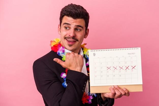 Jonge blanke zakenman die de dagen telt voor vakanties geïsoleerd op roze achtergrondpunten met duimvinger weg, lachend en zorgeloos.