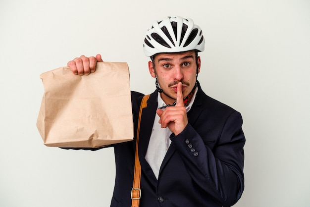Jonge blanke zakenman die een fietshelm draagt en voedsel vasthoudt geïsoleerd op een witte achtergrond, een geheim houdt of om stilte vraagt.