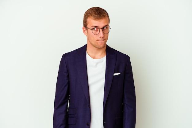 Jonge blanke zakenman geïsoleerd op wit verward, twijfelachtig en onzeker voelt.