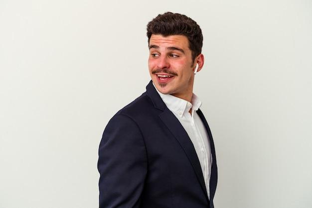 Jonge blanke zakenman met draadloze koptelefoon geïsoleerd op een witte achtergrond kijkt opzij glimlachend, vrolijk en aangenaam.