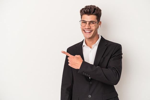 Jonge blanke zakenman met een koptelefoon geïsoleerd op een witte achtergrond glimlachend en opzij wijzend, iets latend op de lege ruimte.