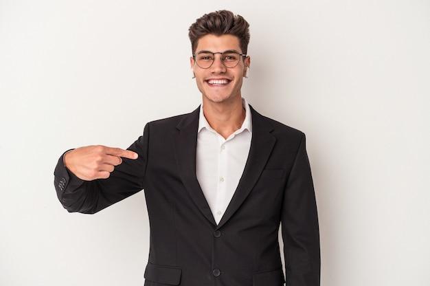 Jonge blanke zakenman met een koptelefoon geïsoleerd op een witte achtergrond persoon die met de hand wijst naar een shirt kopieerruimte, trots en zelfverzekerd?