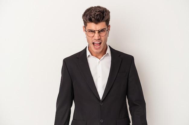 Jonge blanke zakenman met een koptelefoon op een witte achtergrond die erg boos en agressief schreeuwt.